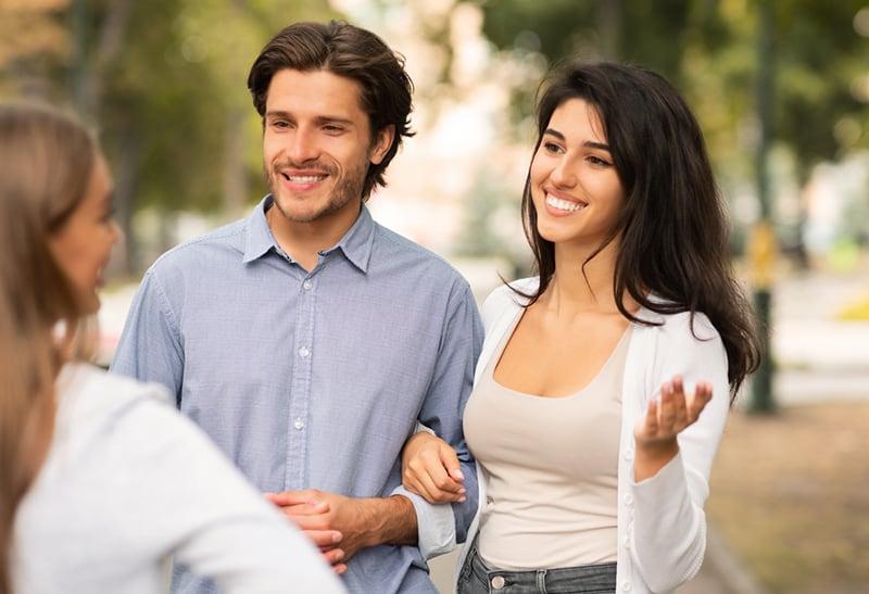 ein Mädchen, das mit einem liebenden Paar spricht, während es auf dem Bürgersteig steht