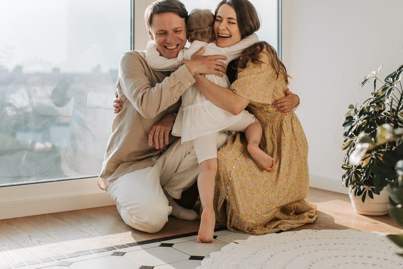 ein Mädchen in den Armen von Mutter und Vater