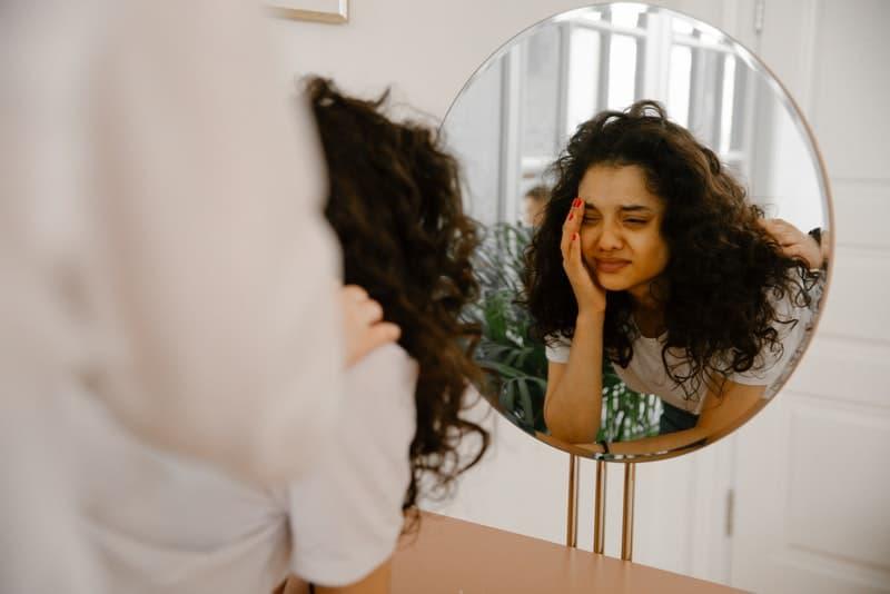 ein Mädchen weint vor einem Spiegel