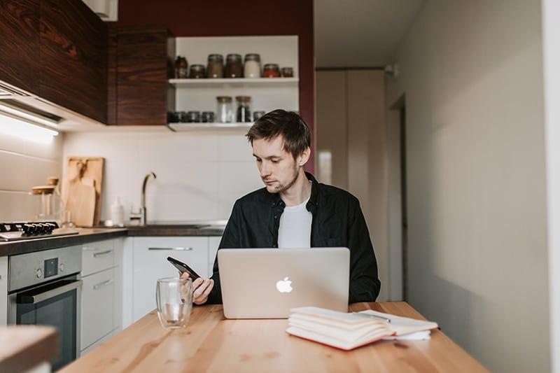 ein Mann, der Smartphone während der Arbeit am Laptop in der Küche betrachtet