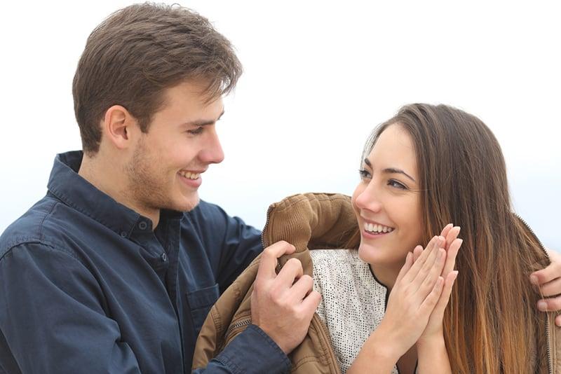 ein Mann, der das lächelnde Mädchen mit seiner Jacke bedeckt, während er draußen steht