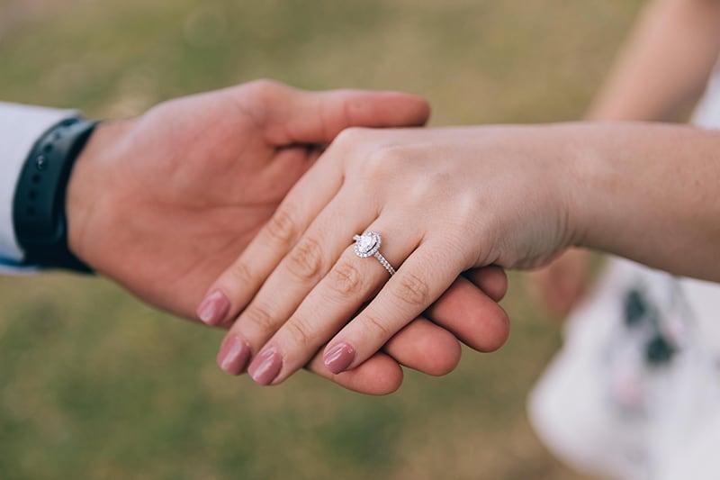 Ein Mann hält die Hand einer Frau mit einem Verlobungsring am Finger