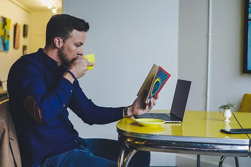 Ein Mann liest ein Buch und trinkt Kaffee, während er am Tisch sitzt