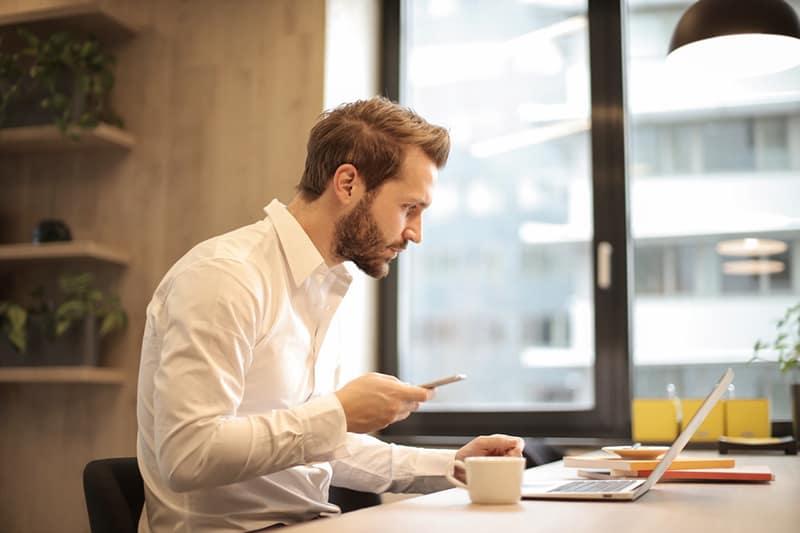 ein Mann, der ein Smartphone hält, während er während der Arbeitszeit einen Laptop betrachtet