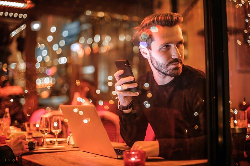 ein Mann, der ein Smartphone hält, während er durch das Fenster schaut, während er im Café sitzt
