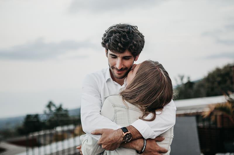 Ein Mann umarmte eine Frau, die ihn auf die Wange küssen wollte