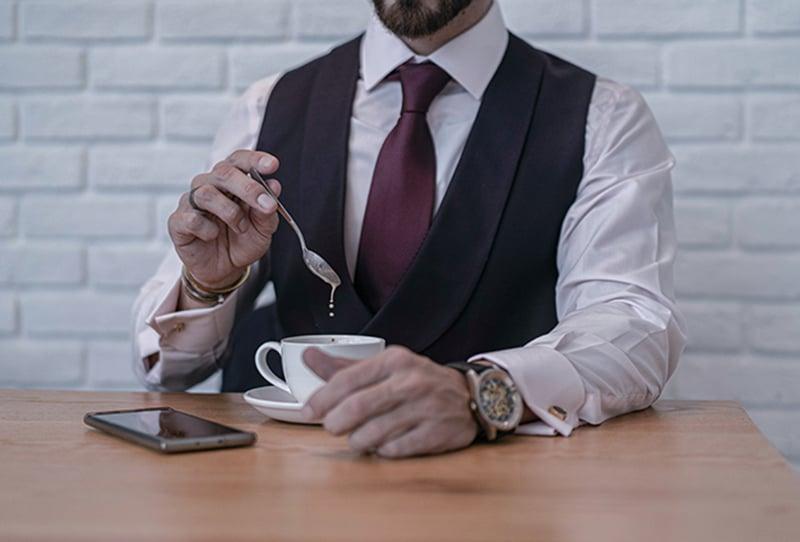 ein Mann, der einen Teelöffel hält, während er einen Kaffee auf dem Tisch in der Nähe des Smartphones mischt