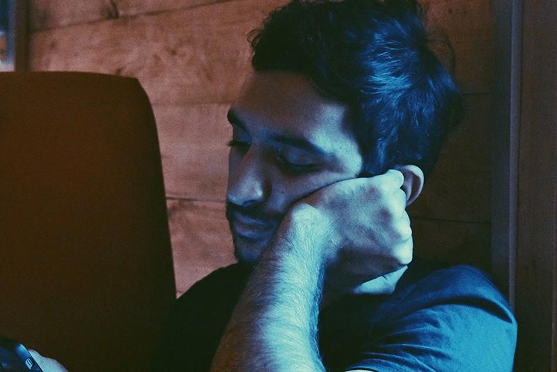 Ein Mann, der im Dunkeln auf ein Smartphone schaut und sich an die Wand lehnt