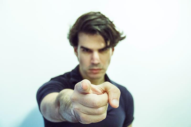 ein Mann, der mit einem Finger zeigt und ernst aussieht