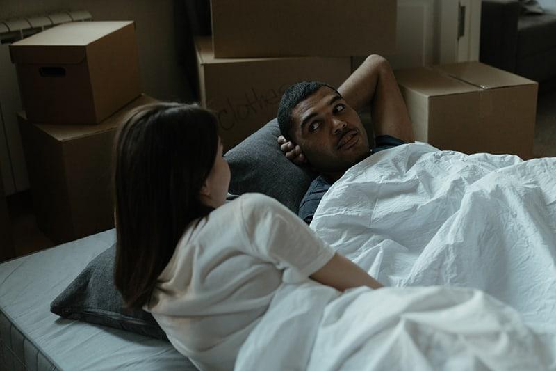 Ein Mann schaut zu seiner Freundin, während er auf dem Bett liegt