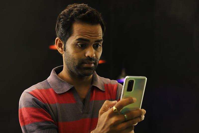 ein Mann im Poloshirt, der Smartphone betrachtet und überrascht schaut