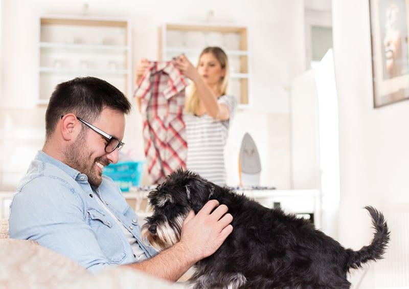Ein Mann sitzt auf dem Sofa und kuschelt einen Hund, während die Frau bügelt und die Hausarbeit erledigt