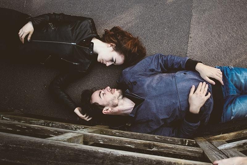 Ein Mann und eine Frau liegen auf der Betonoberfläche und stehen sich gegenüber