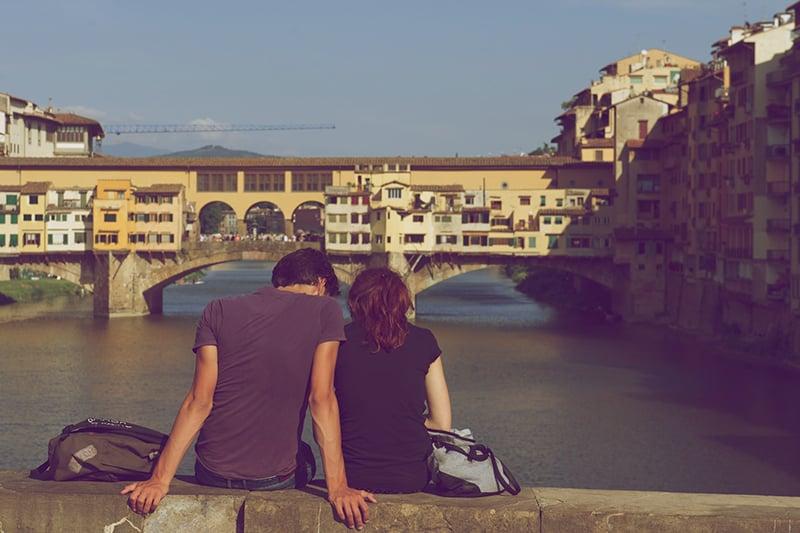 Ein Mann und eine Frau sitzen dicht beieinander vor dem Gewässer