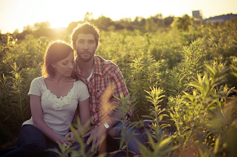 ein Paar, das während des Sonnenuntergangs auf dem Feld sitzt