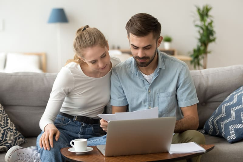 Ein Paar sitzt auf der Couch und schaut sich die Dokumente an