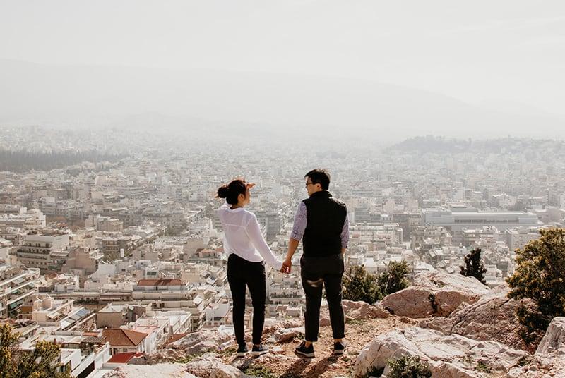 ein Paar steht auf dem Felsen gegenüber der Stadt