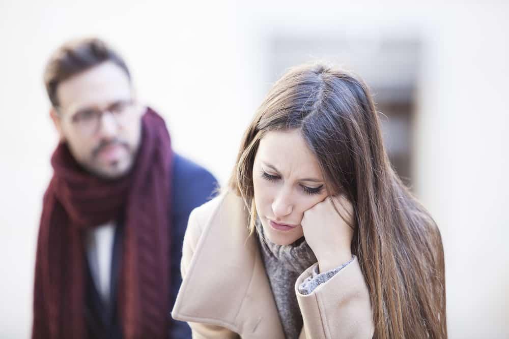 ein Porträt einer traurigen Frau, die hinter einem Mann steht