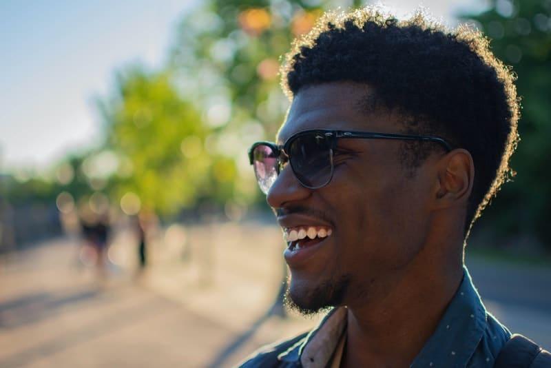 ein Porträt eines lächelnden Mannes mit Sonnenschirmen
