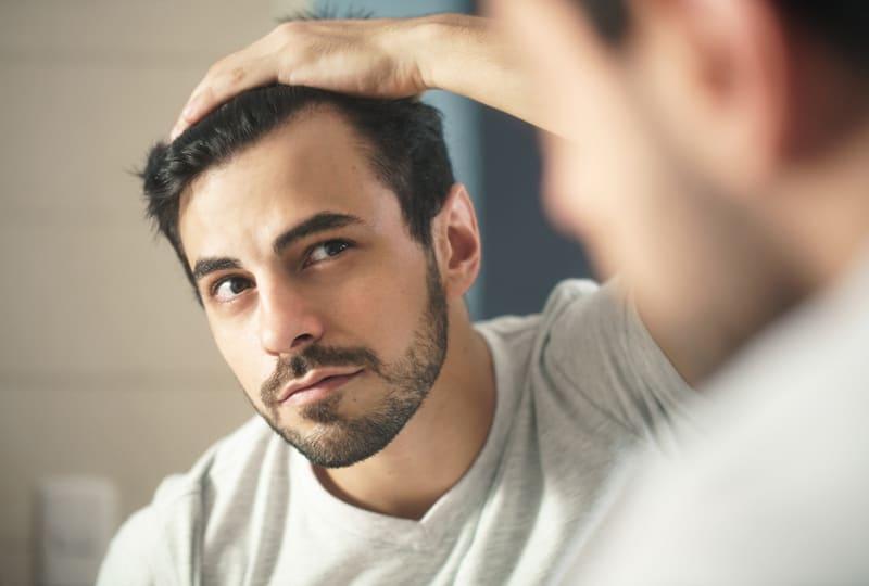Ein bärtiger Mann, der sich im Spiegel nach den ersten grauen Haaren umschaut