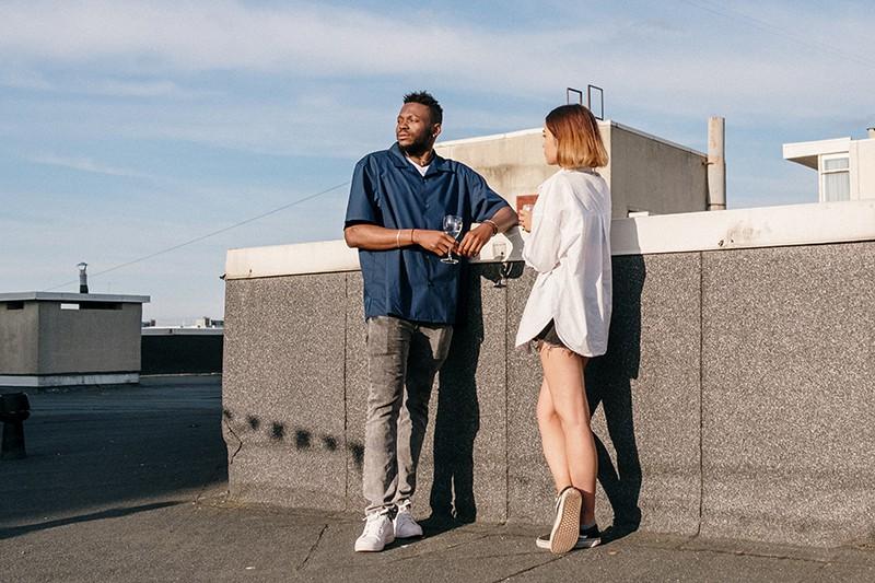 Ein ernster Mann, der beiseite schaut, während er mit einem Mädchen steht und zusammen auf dem Dach etwas trinkt