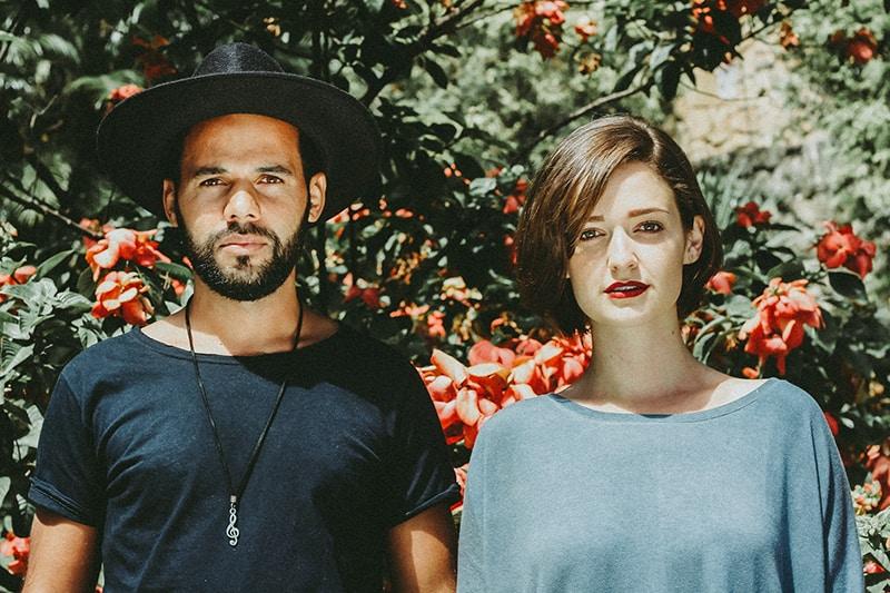 Ein ernster Mann und eine Frau stehen nahe beieinander vor einem Blumenbaum