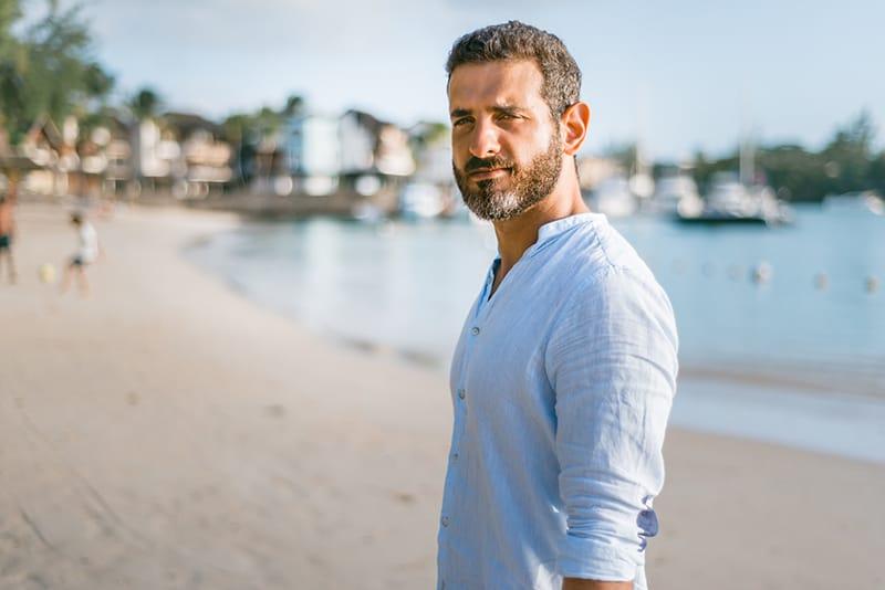 ein gutaussehender Mann, der tagsüber am Strand steht