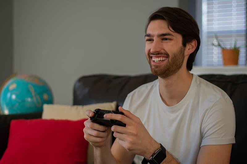 ein lächelnder Mann, der Videospiele spielt, während er auf der Couch sitzt