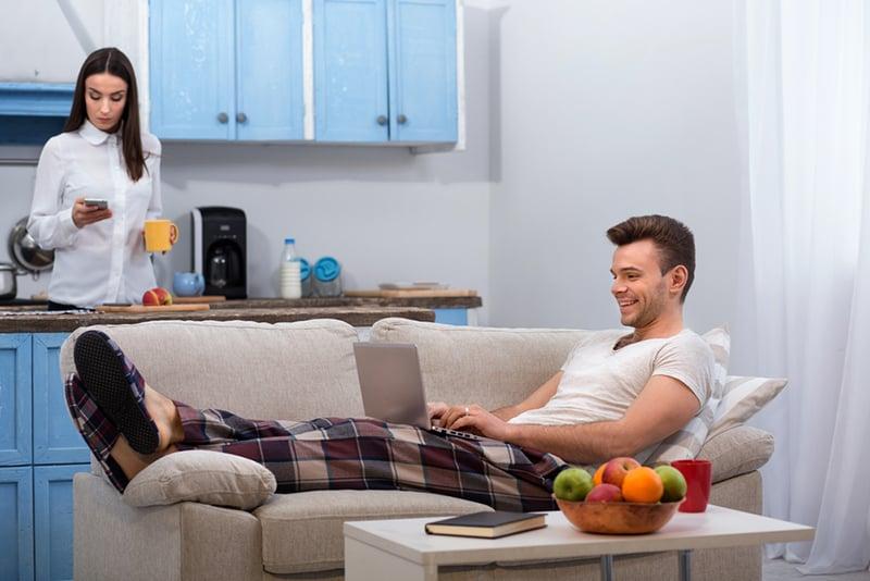 Ein lächelnder Mann, der auf der Couch liegt und einen Laptop benutzt, während seine Frau sich darauf vorbereitet, ins Büro zu gehen