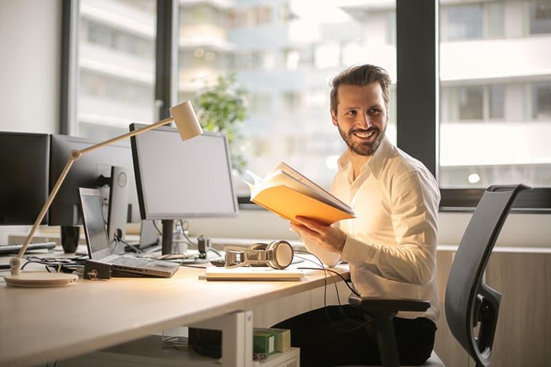 ein lächelnder Mann, der ein Notizbuch hält, während er im Büro sitzt