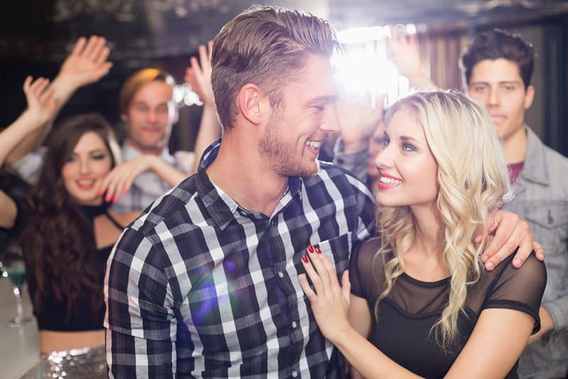 Ein lächelnder Mann umarmt und schaut eine Frau, während er zusammen im Club steht, umgeben von Menschen