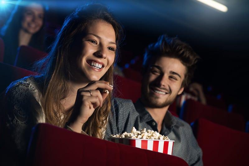 ein lächelnder Mann, der eine lächelnde Frau schaut, während er zusammen im Kino sitzt