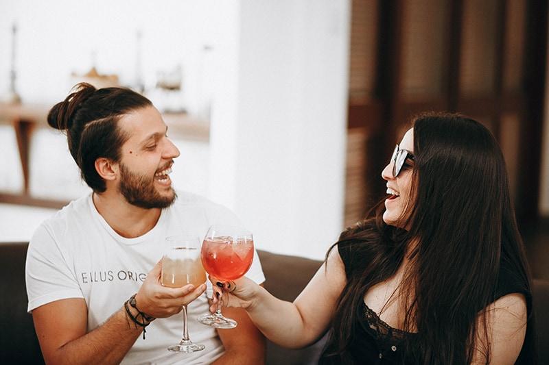 ein lächelnder Mann und eine Frau, die einen Toast haben, während sie auf der Couch sitzen