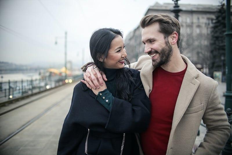 ein lächelndes Paar, das sich ansieht, während es sich umarmt und auf dem Bürgersteig geht