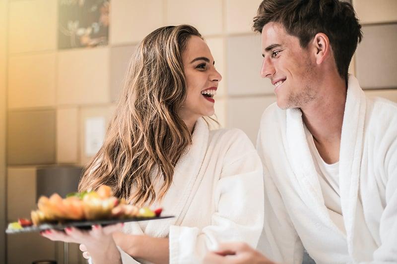ein lächelndes Paar, das einander schaut, während Frau einen Teller mit Früchten im Bett hält