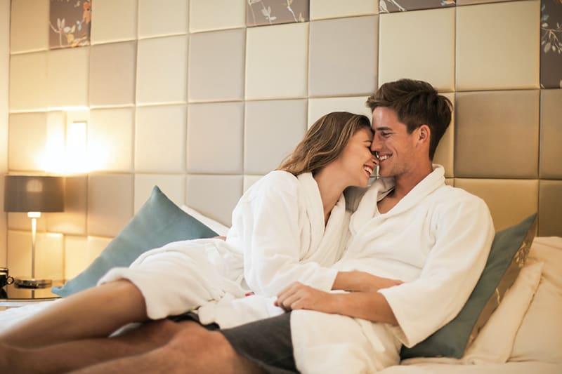 Ein lächelndes Paar umarmt sich, während es auf dem Bett liegt