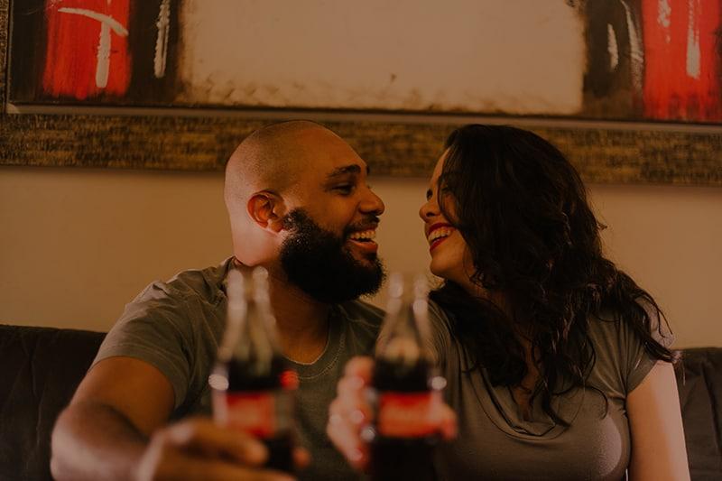 Ein lächelnder Mann und eine Frau schauen sich an, während sie auf ein Date einen Toast mit Getränken trinken