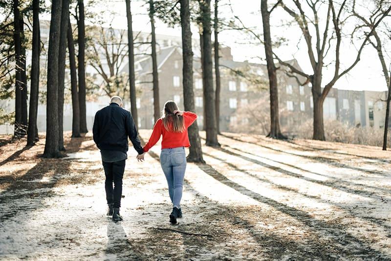 ein liebendes Paar Händchen haltend beim Gehen im Park