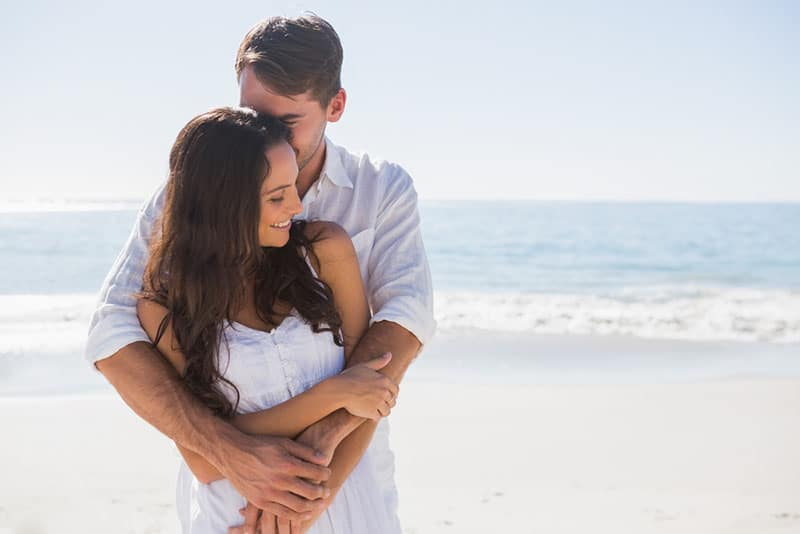 ein liebendes Paar, das am Strand kuschelt