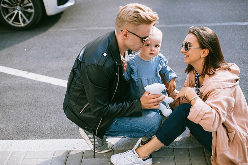 ein liebevolles Paar, das mit seinem Baby auf dem Betonboden sitzt, während es sich von einem Spaziergang ausruht