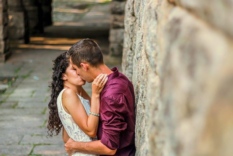 ein liebevolles Paar, das sich küsst und umarmt, während es sich an die Steinmauer lehnt