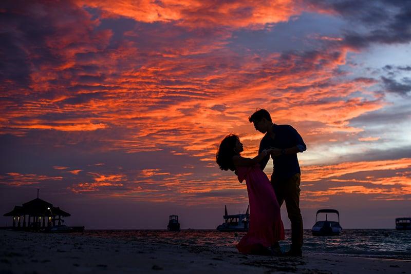 Ein Paar tanzt am Strand während des Sonnenuntergangs