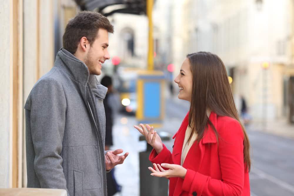 ein positives Mädchen, das mit einem lächelnden Mann spricht, der auf dem Bürgersteig steht