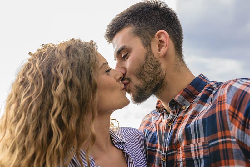 ein selbstbewusster Mann, der eine Frau bei einem Date küsst
