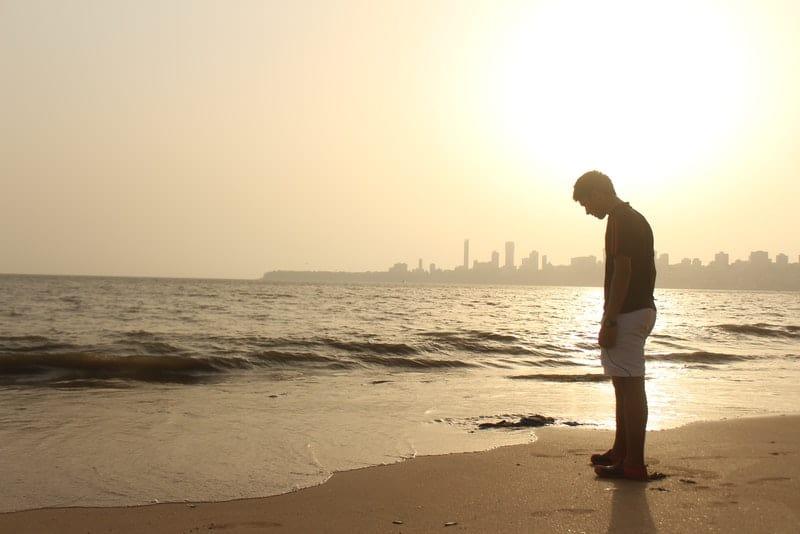 ein trauriger Mann, der am Strand steht
