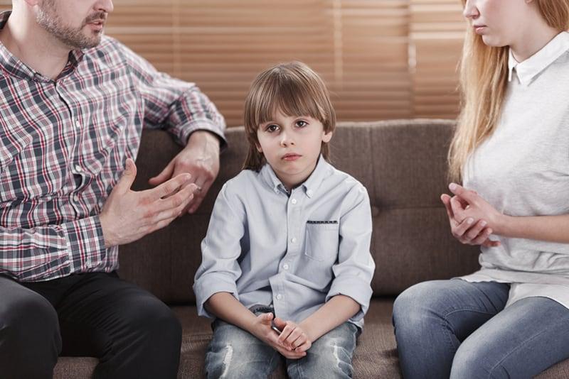 ein trauriges Kind, das zwischen seinen Eltern sitzt, während sie mit ihm sprechen