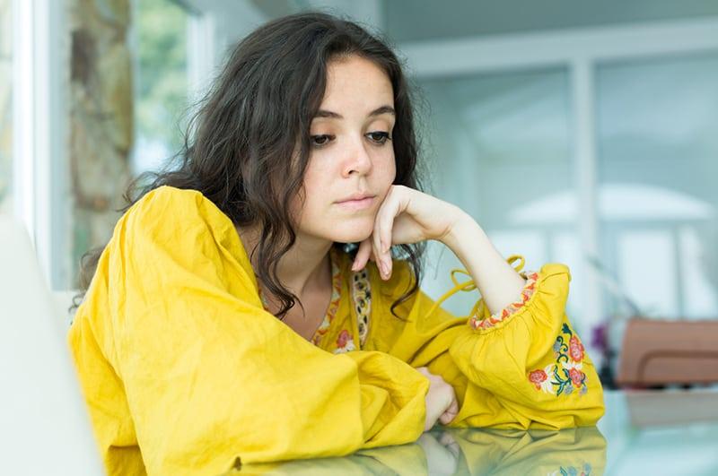 Ein trauriges Mädchen saß mit gesenkten Augen am Tisch