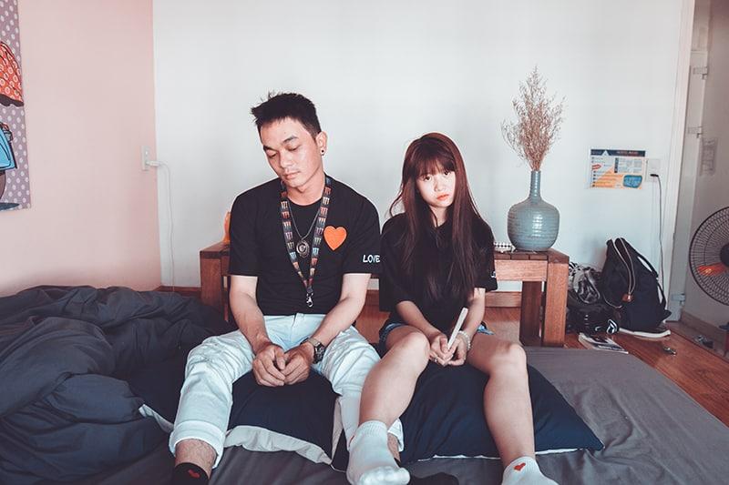 ein unglückliches Paar sitzt auf dem Bett ohne zu reden