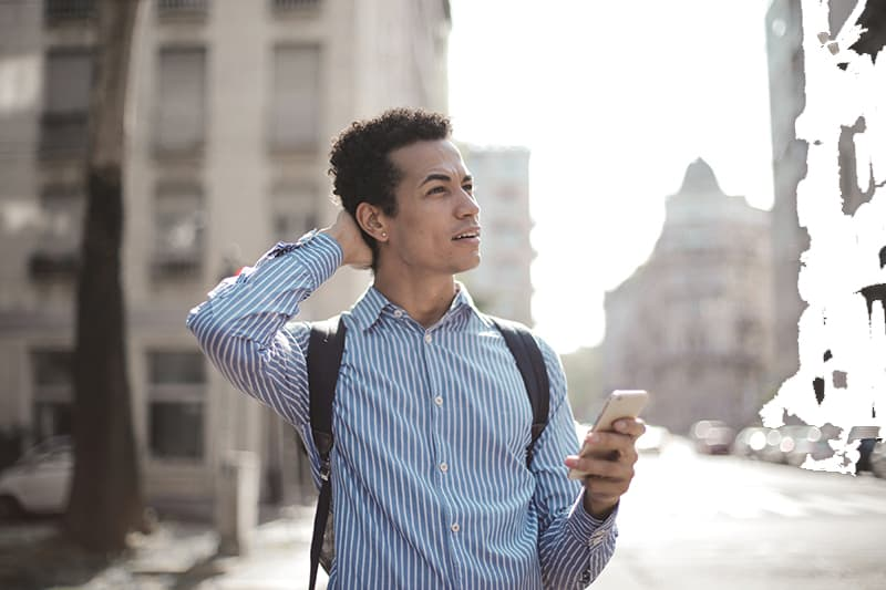 Ein verwirrter Mann, der auf der Straße steht und sich mit einem Smartphone in der Hand umschaut