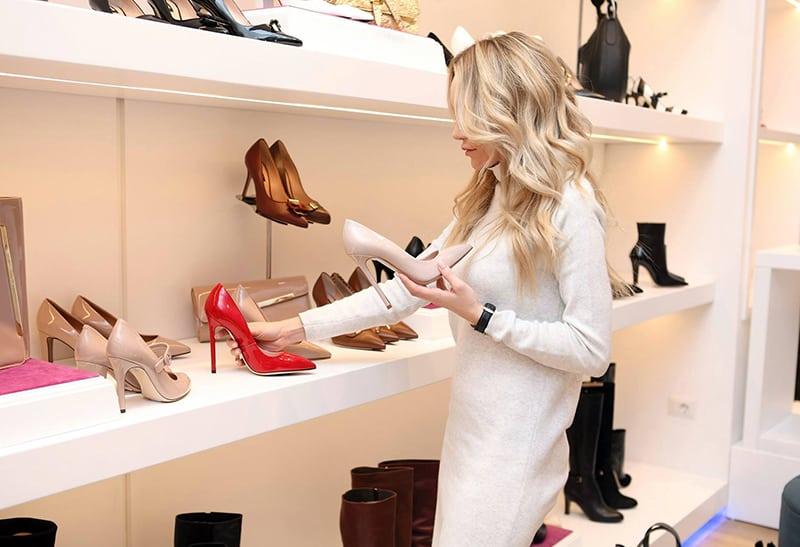 eine Frau, die High Heels Schuhe im Schuhgeschäft sucht